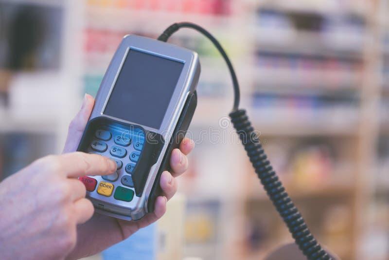 Terminal del pago en una tienda, pagando por la tarjeta imagen de archivo