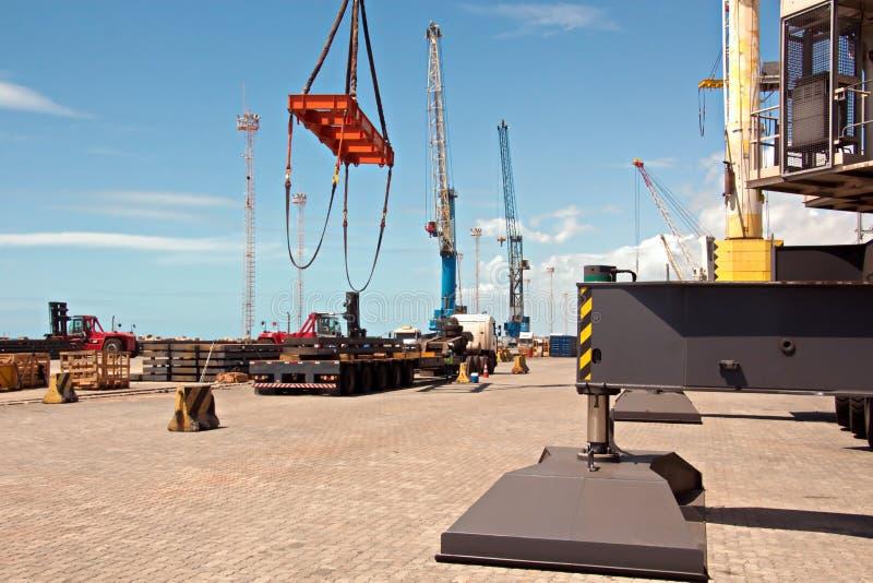Terminal do transbordamento para produtos de aço de carregamento às embarcações do mar usando guindastes da costa e o equipamento fotografia de stock