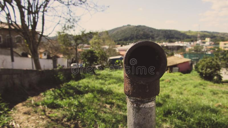 Isolated vertical rusty pipe end. The terminal end of rusty pipe placed vertically on a meadow, closeup, broken, industrial, color, corrosion, conduit, pipeline stock images