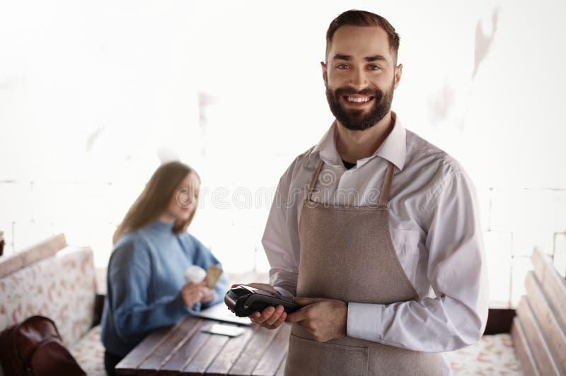 Terminale di pagamento della tenuta del cameriere vicino alla tavola con il cliente fotografia stock libera da diritti