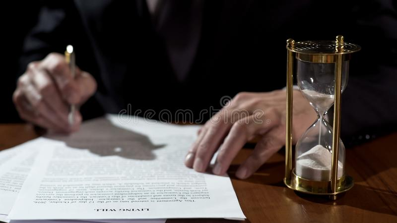 Terminally ill man signing living will before medical care, leaving heritage stock images