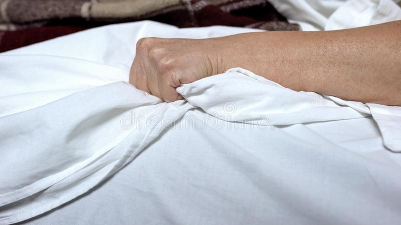 Terminally-ill woman clenching bedsheets feeling terrible pain, death convulsion stock image