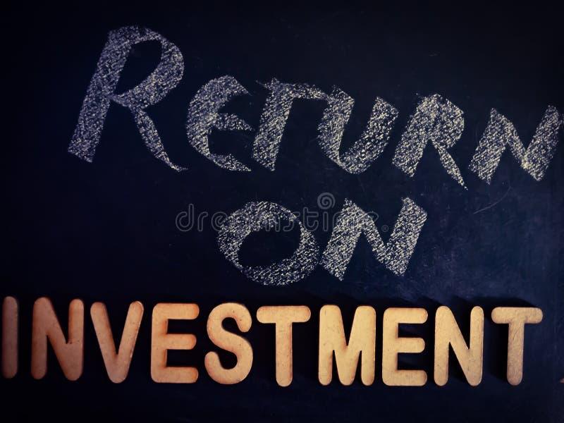 termine di ritorno sull'investimento visualizzato nel concetto di cartone con una trama in alfabeto di legno fotografia stock libera da diritti