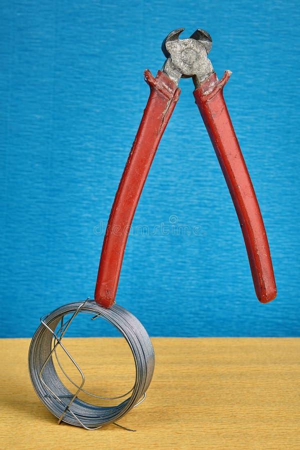 Termine los alicates del corte de la pinza que se colocan verticales en el alambre de la bobina fotos de archivo libres de regalías