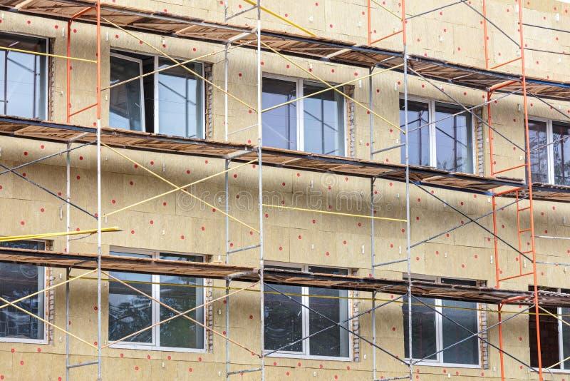 Termisk isolering av husv?ggen med mineralisk ull material till byggnadsst?llning n?ra fasad av en byggnad fotografering för bildbyråer