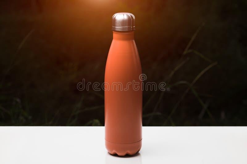 Termo bottiglia inossidabile per acqua, tè e coffe, sulla tavola bianca Fondo scuro dell'erba con effetto di luce solare Colore d fotografie stock libere da diritti