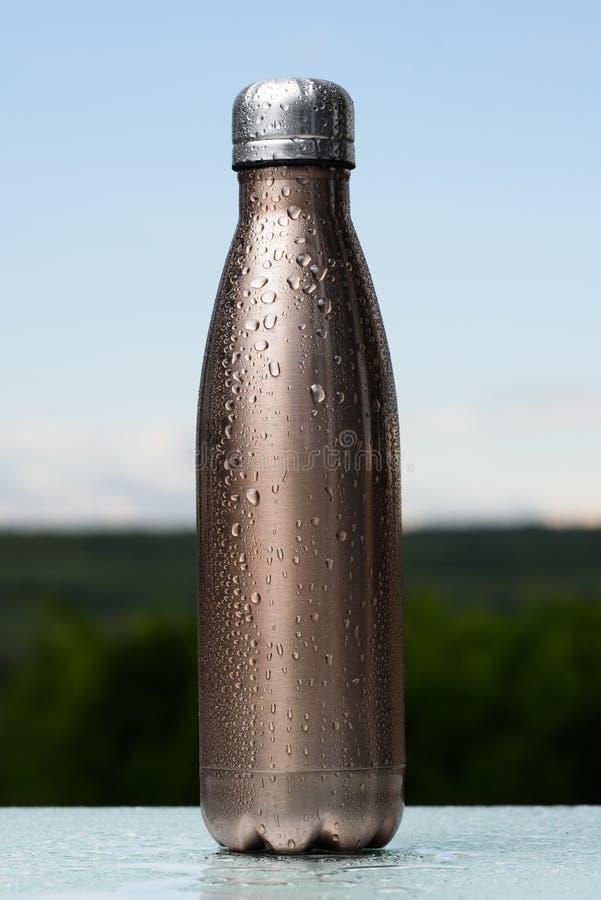 Termo bottiglia inossidabile, spruzzata con acqua Cielo e foresta su fondo Sullo scrittorio di vetro Termos di colore di maro immagini stock
