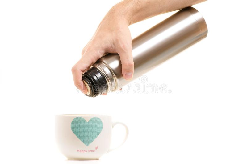 Termo con una taza en manos del ` s de los hombres fotografía de archivo libre de regalías