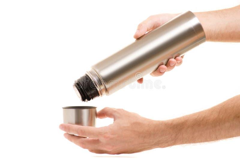 Termo con una taza en manos del ` s de los hombres fotografía de archivo