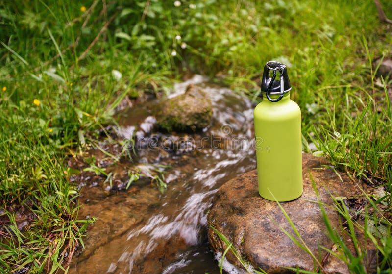 Termo de acero con agua en el río cercano de piedra de la montaña fotos de archivo libres de regalías