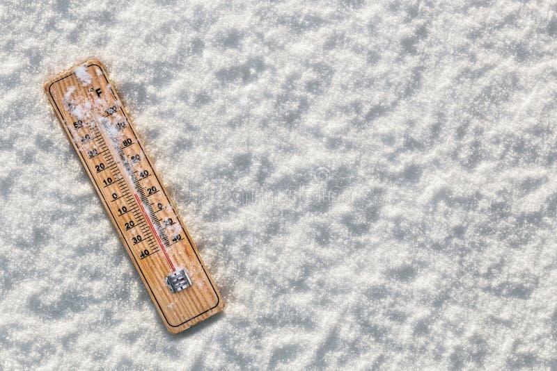 Termometer i snön med att frysa temperaturer arkivbilder