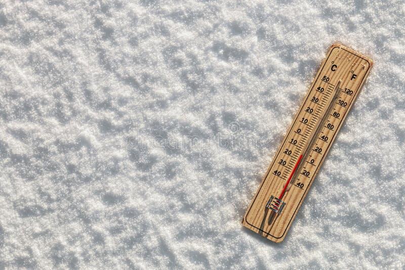 Termometer i snön med att frysa temperaturer arkivbild