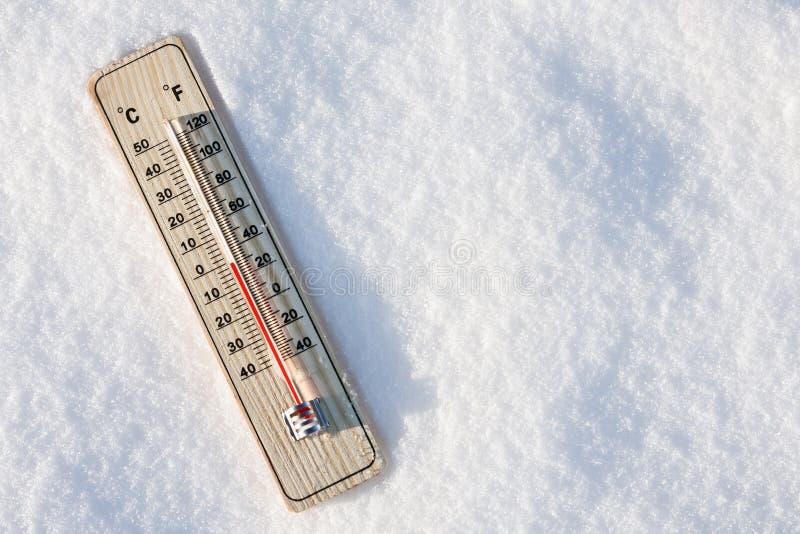 Termometer i snowen med nolltemperaturen royaltyfri bild