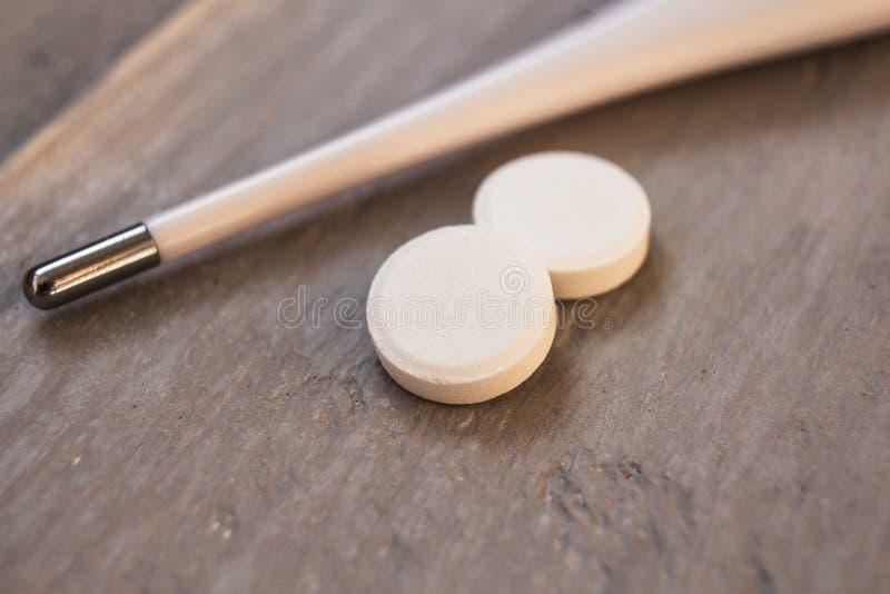 Termometer med vita preventivpillerar på träbakgrund arkivfoto