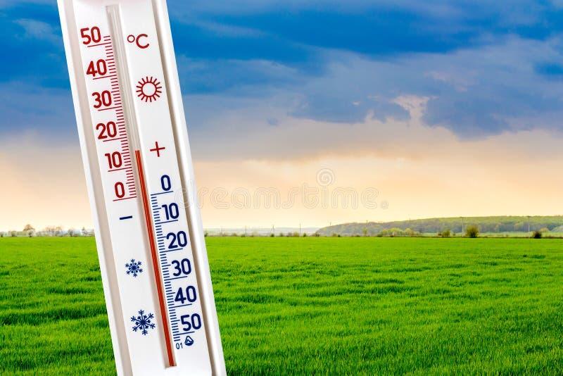 Termometern på bakgrunden av fältet visar 15 grader av värme Mätning av lufttemperature_ arkivfoto