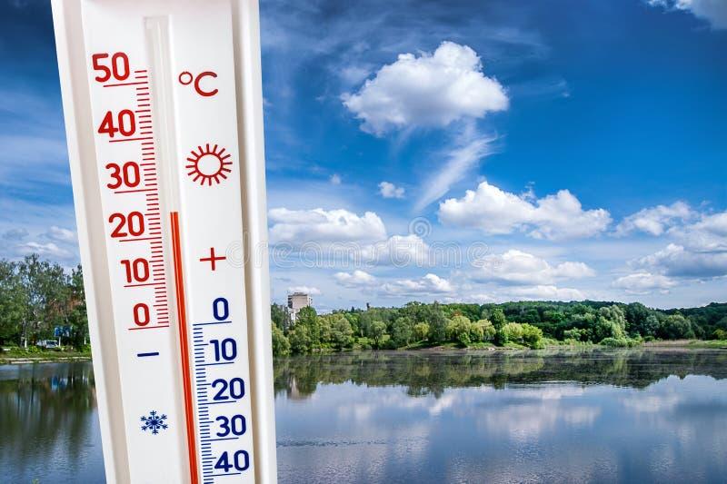 Termometern på bakgrunden av sommarlandskapet med en flod på en solig dag visar 25 grader av värme Sommarheat_ royaltyfri fotografi