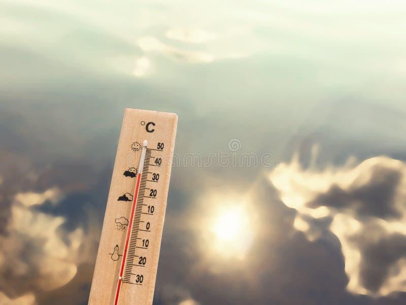 Termometervisning 30 grader av värme mot bakgrunden av sjövatten med reflexionen av moln och solen arkivbilder
