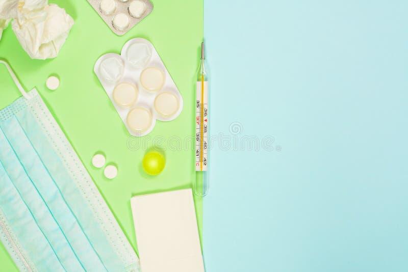 Termometr, chusteczki, medycyny, medyczna maska na zielonym błękitnym tle Zimny i grypowy traktowania pojęcie z fotografia stock