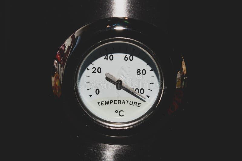 Termometro analogico vecchio stile sullo sfondo metallico concetto di alta temperatura fotografia stock