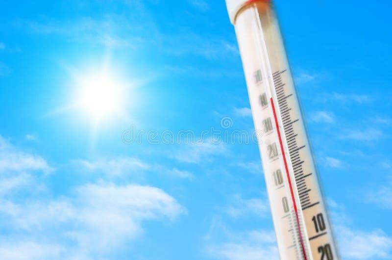 Termometro contro lo sfondo di un'incandescenza calda blu delle nuvole e del sole, concetto di caldo fotografie stock libere da diritti