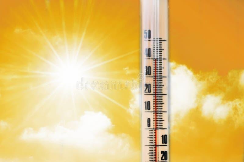 Termometro contro lo sfondo di un'incandescenza calda di giallo arancio delle nuvole e del sole, concetto di caldo immagine stock