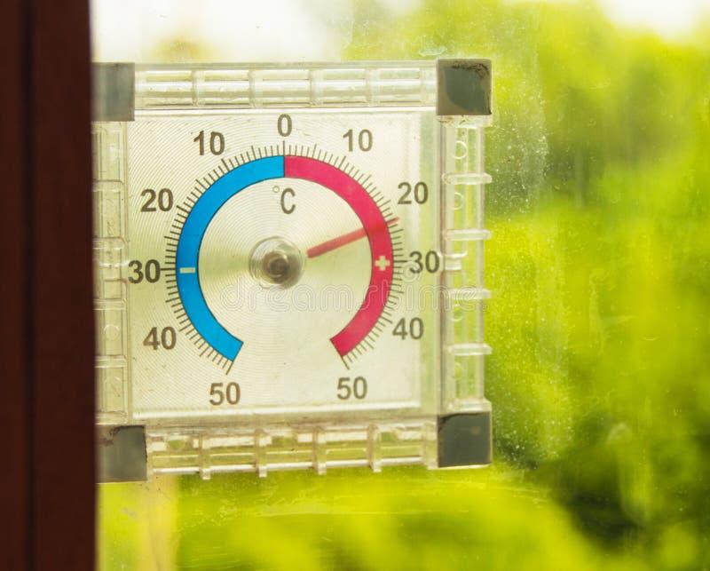 Termometro della via che appende sulla finestra e sulle manifestazioni la temperatura dell'aria di estate contro gli alberi verdi immagini stock libere da diritti
