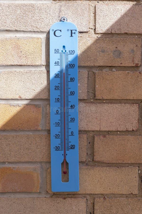 Termometro di plastica blu del giardino che mostra temperatura elevata fotografia stock libera da diritti