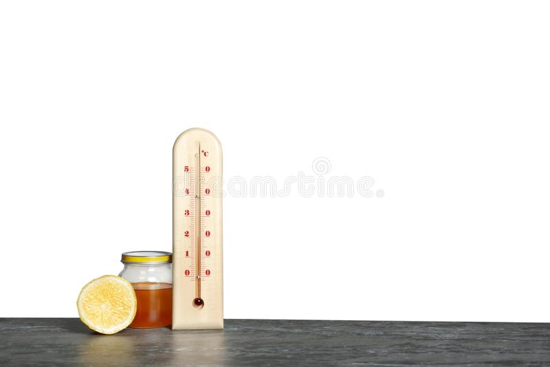 Termometro, limone e miele sulla tavola contro fondo grigio immagine stock