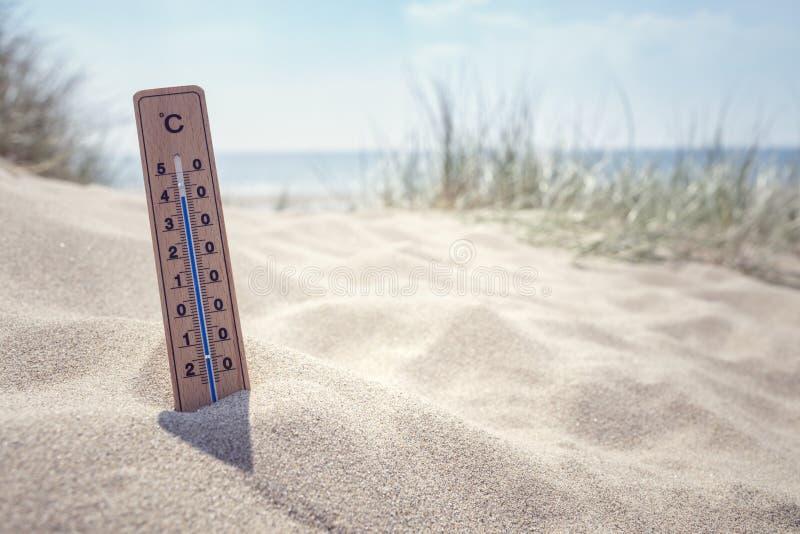 Termometro sui precedenti della spiaggia fotografia stock