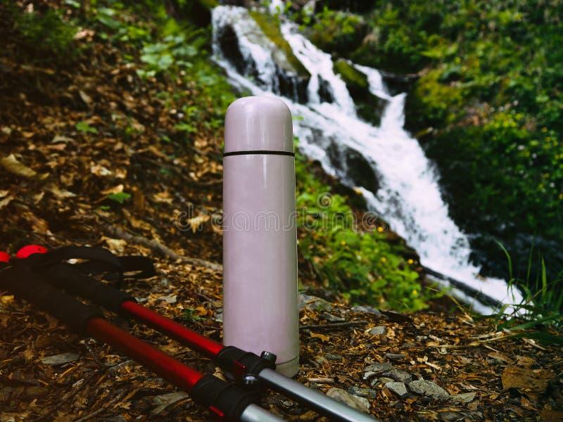 Termos e pali di trekking al fondo della cascata immagini stock libere da diritti