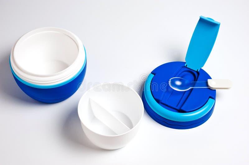 Termos per alimento nuovo, di plastica, blu con il cucchiaio su fondo bianco fotografie stock