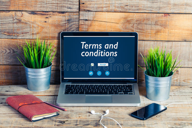 Terms and conditions message in a laptop computer. Workplace stuff on the desk. Terms and conditions message in a laptop screen stock photos
