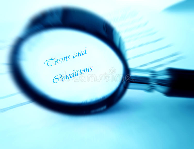 Terms and conditions under magnifier. Read the small print - A conceptual image of a magnifying glass used to read the fine prints of a document, with the focus royalty free stock photos