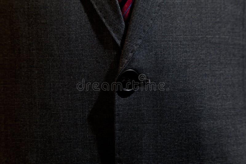 Terno cinzento com botão do terno foto de stock
