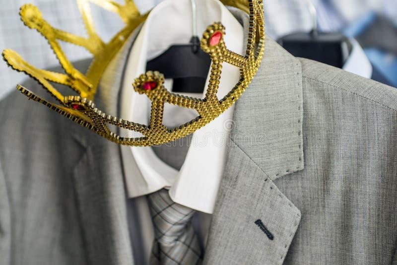 Terno de negócio com uma coroa do ouro que pendura em um gancho A roupa é uma pessoa bem sucedida Conceito do negócio metaphor imagem de stock royalty free
