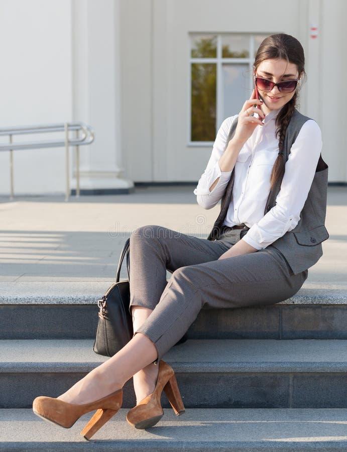 Terno de negócio da mulher, bolsa, telefone esperto foto de stock