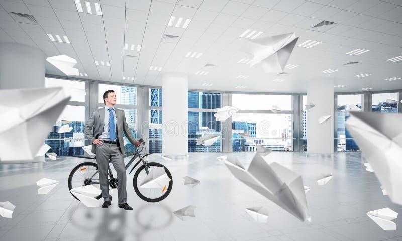 Terno de negócio vestindo do homem novo com bicicleta fotos de stock