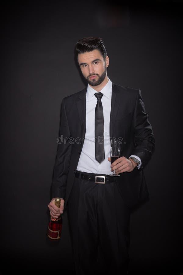 Terno de vidro do vinho do álcool da garrafa do homem novo elegante imagens de stock