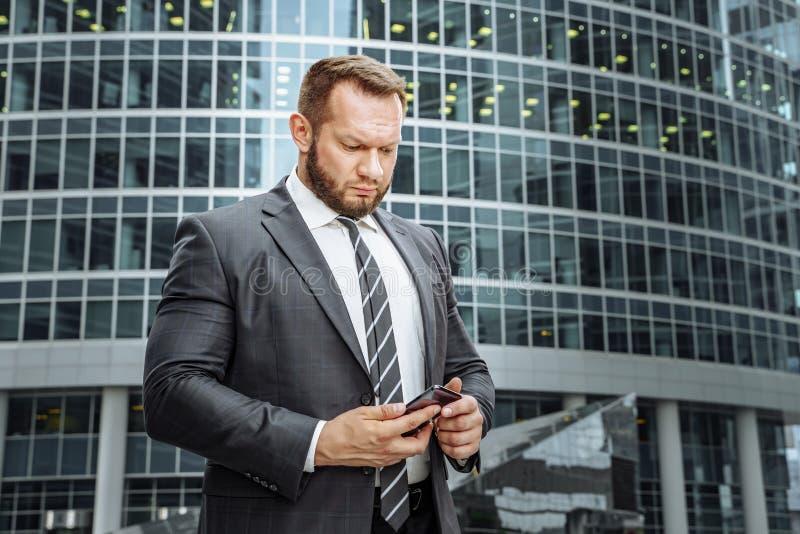 Terno do homem de negócio e smartphone vestindo da utilização perto do escritório imagem de stock royalty free