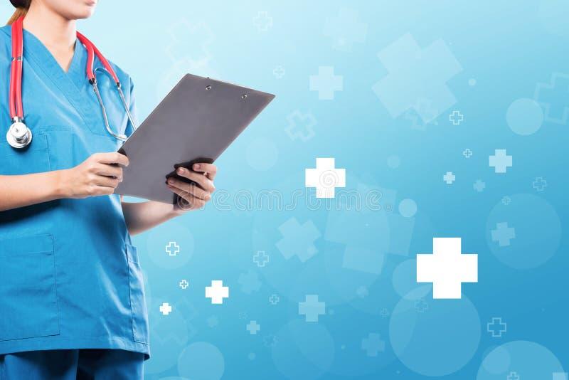 Terno fêmea do médico que guarda um formulário paciente com hosp azul fotografia de stock royalty free