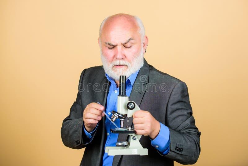 Terno formal do homem maduro com microscópio Trabalho doutoral e emprego pos-doctoral Projetos do doutorado da biologia molecular fotos de stock royalty free