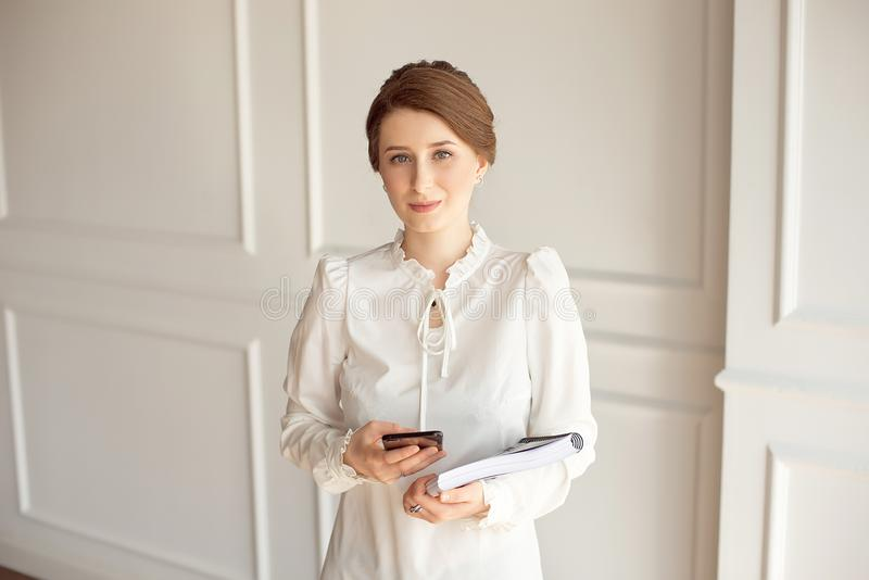 Terno vestindo da mulher de negócio da foto, olhando o smartphone e guardando originais nas mãos fotografia de stock royalty free
