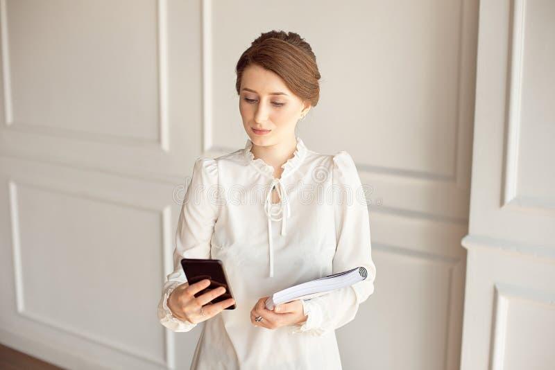 Terno vestindo da mulher de negócio da foto, olhando o smartphone e guardando originais nas mãos imagem de stock royalty free