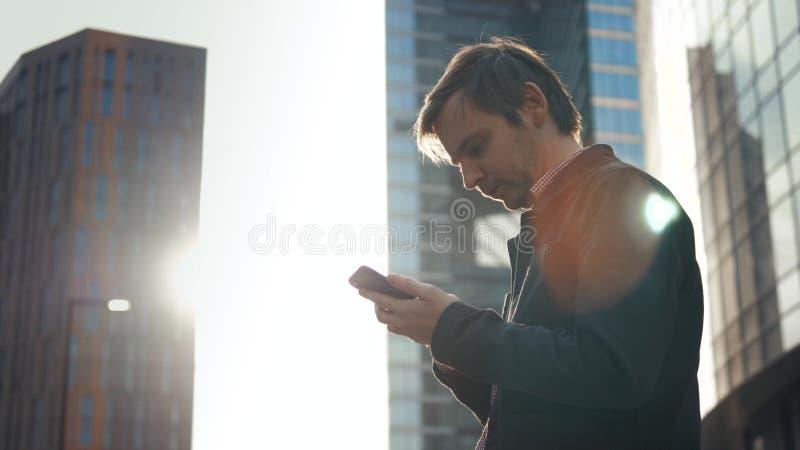 Terno vestindo de sorriso feliz do homem de negócios e utilização do smartphone moderno perto do escritório no amanhecer, emprega foto de stock