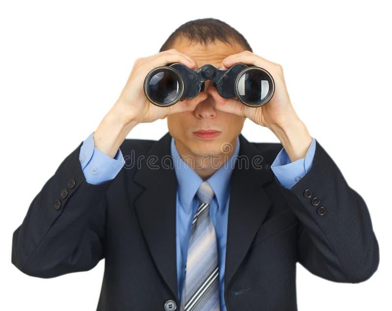Terno vestindo do homem de negócio com o laço azul com binóculos fotos de stock