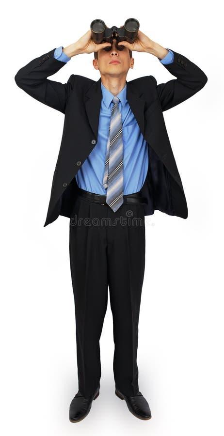 Terno vestindo do homem de negócio com o laço azul com binóculos fotografia de stock