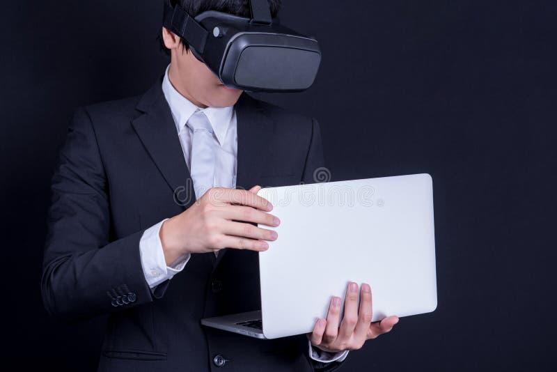 Terno vestindo do homem de negócio que joga óculos de proteção da realidade virtual fotografia de stock