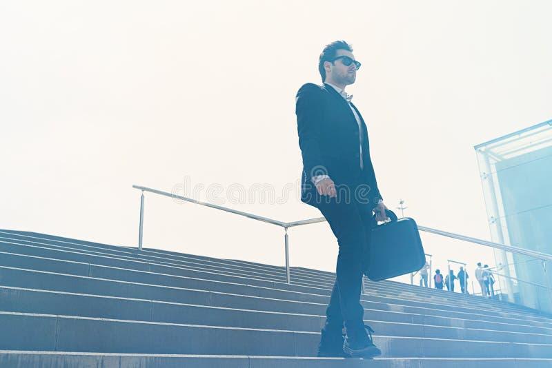 Terno vestindo e corredor do homem de negócios confidencial novo rapidamente em baixo Tiro horizontal do ar livre foto de stock