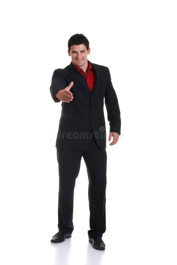 Terno vestindo masculino novo que estica a mão para o aperto de mão fotografia de stock royalty free