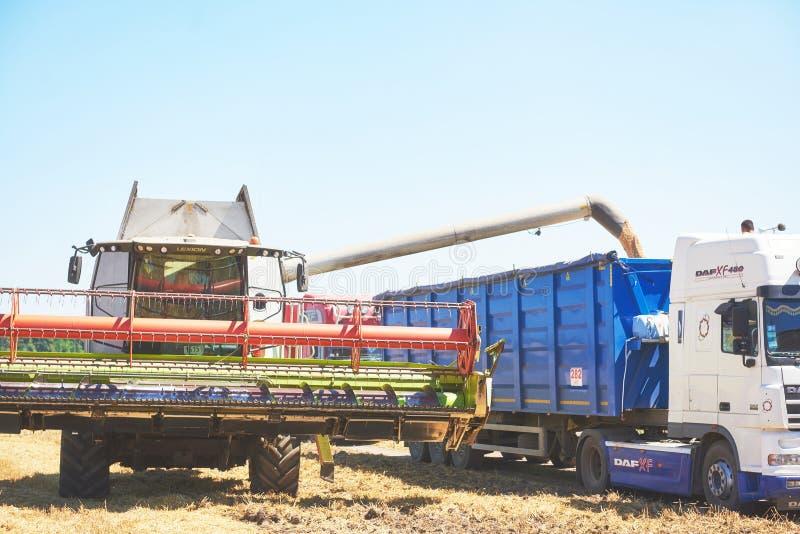TERNOPIL - 20-ОЕ ИЮЛЯ: Жатка зернокомбайна в действии на пшеничном поле Сбор процесс собирать зрелый урожай от стоковое фото rf